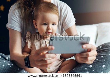 Nine-month-old baby girl sits with her mother on bed and looks on smartphone cartoons, plays game. Child is talking to her grandmother via video link. Mom shows her daughter pictures on phone screen.