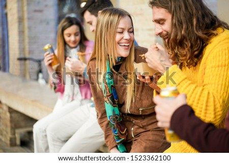 Happy friends eating street food outdoor - Young trendy people having fun together drinking and laughing around downtown streets - City lifestyle and party concept - Focus on blond girl face #1523362100
