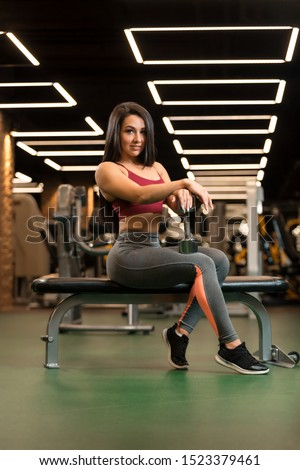 Beautiful fitness brunette girl is sitting with dumbbell and posing #1523379461