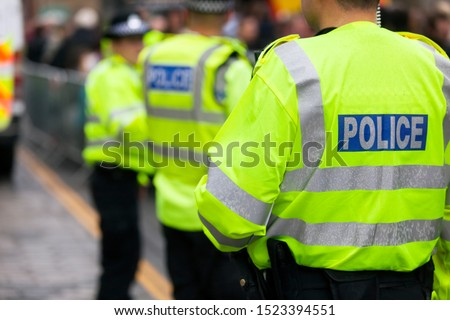 Police in hi-visibility jackets policing crowd control at a UK event Royalty-Free Stock Photo #1523394551