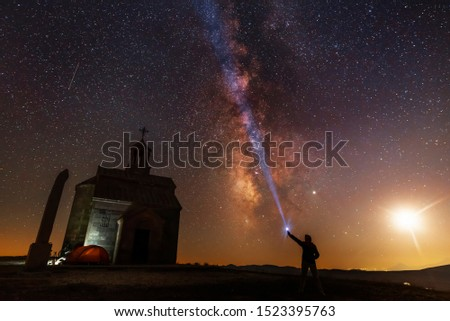 Beautiful night landscape. Small chapel on the hill. Behind chapel bright milky way and moon. Person silhouette with flashlight illuminate starry sky. #1523395763