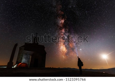 Beautiful night landscape. Small chapel on the hill. Behind chapel bright milky way and moon. Person silhouette with flashlight illuminate starry sky. #1523395766