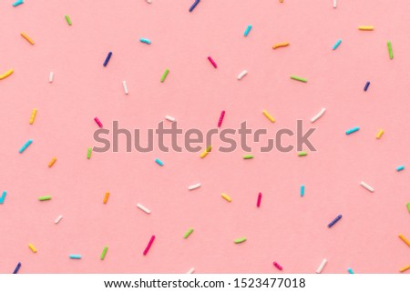 trendy pattern of colorful sprinkles for background of design banner, poster, flyer, card, postcard, cover, brochure over pink  Royalty-Free Stock Photo #1523477018