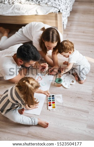 two parents teaching their kids names of colour and forms while painting on the floor. education #1523504177
