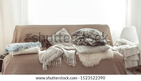 Modern interior of the living room with a sofa and decorative items . Decorative pillows and blankets. Coziness and comfort at home . #1523522390