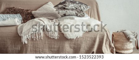Modern interior of the living room with a sofa and decorative items . Decorative pillows and blankets. Coziness and comfort at home . #1523522393