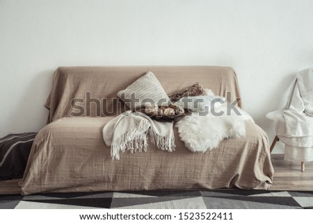 Modern interior of the living room with a sofa and decorative items . Decorative pillows and blankets. Coziness and comfort at home . #1523522411