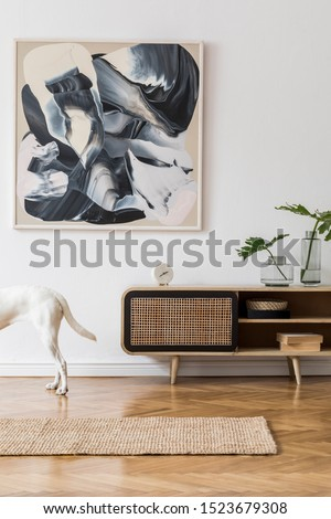 Scandinavian and design home interior of living room with wooden commode, books, plants and elegant accessories. Stylish home decor. Template. Mock up poster paintings. Dog's standing on the carpet.  #1523679308