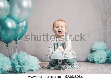 Baby sweet littleboy gril green blue cake smash eating bif cake decoration clean background  Royalty-Free Stock Photo #1523688086