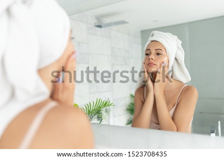 Young beautiful woman using skin face cream moisturizing lotion after taking bath. Pretty attractive girl wearing towel on head standing front of mirror in home bathroom. Daily hygiene and skincare #1523708435