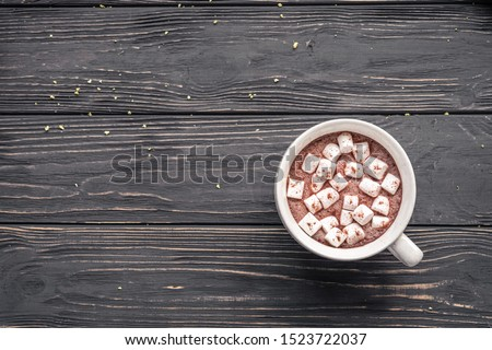 Cocoa chocolate cup with hot drink and white marshmallow on wood desk cozy background, cacao in mug on brown wooden rustic table, holiday coffee house shop, above top overhead view, copy space Royalty-Free Stock Photo #1523722037