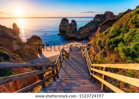 Sunrise at Camilo beach in Lagos, Algarve, Portugal. Wooden footbridge to the beach Praia do Camilo, Portugal. Picturesque view of Praia do Camilo beach in Lagos, Algarve region, Portugal. #1523724197