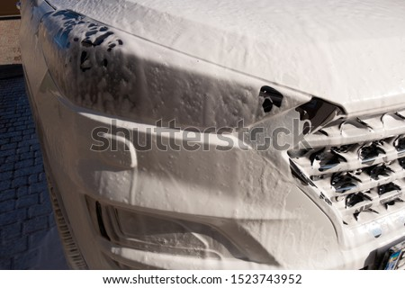 A fragment of the new white crossover model at the time of washing with car shampoo #1523743952