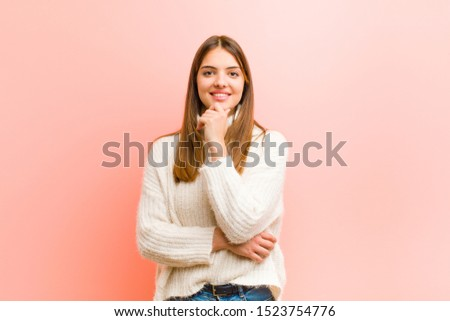 young pretty woman looking happy and smiling with hand on chin, wondering or asking a question, comparing options against pink background #1523754776