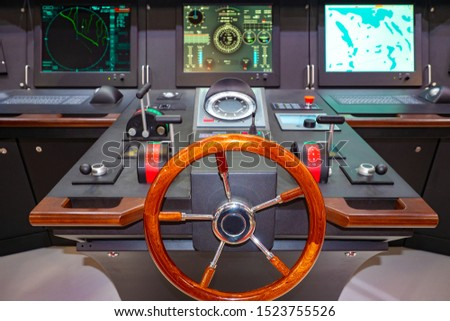 The helm of a modern boat. Captain's bridge. Management of the ship. Equipment for marine vessels.Boat management training. Modern boat.The place of the captain of the ship. Modern wood steering wheel #1523755526