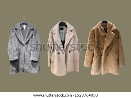 Fashionable winter jacket with fur. Composition of clothes isolated on green. Flat lay, top view, copy space. Ladies' Trench Coat. Winter clothes pattern. Strict classic brown coat. Banner concept #1523764850