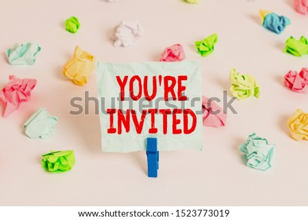 Handwriting text You Re Invited. Concept meaning Please join us in our celebration Welcome Be a guest Colored crumpled papers empty reminder white floor background clothespin. #1523773019