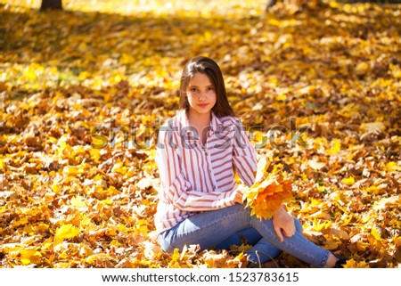 Portrait of a young beautiful girl with yellow maple leaves posing on a background of an autumn park #1523783615