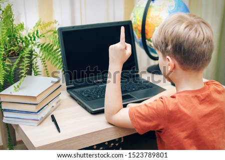 schoolboy sitting at laptop pointing finger up doing homework. back view. selective focus #1523789801