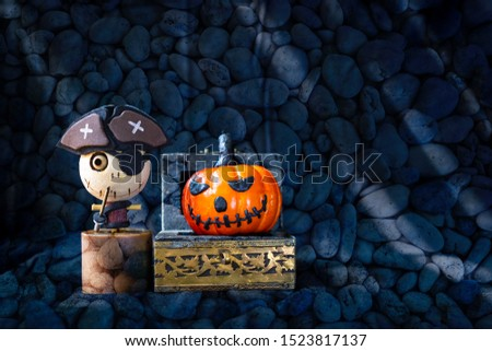 Halloween concept background, wooden pirate ghost and smiling halloween pumpking in treasure box over blurred stone pattern background, halloween decoration item #1523817137