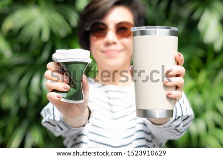 A stylish beautiful woman holding takeaway coffee cup in both hands, one is a single use paper cup with plastic lid the other one is a reusable stainless tumbler. Say no to plastic, No straw, 0 waste  #1523910629