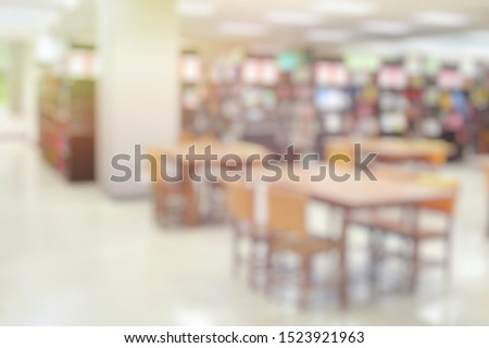 Blurred of the interior of the public library with wooden tables, chairs and books in bookshelves. Education and book's day background concept. #1523921963