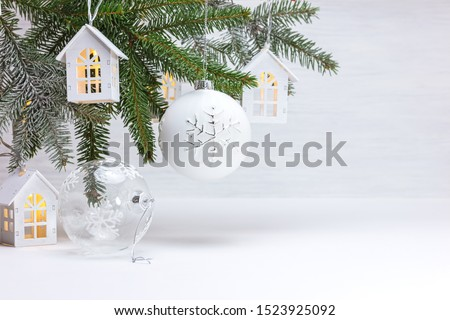 beautiful new year holiday background with christmas tree branch, wooden decorative toy houses garland and glass balls #1523925092