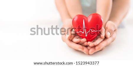 An adult, mother and child hold a red heart in their hands. Concept for charity, health insurance, love, international cardiology day. #1523943377