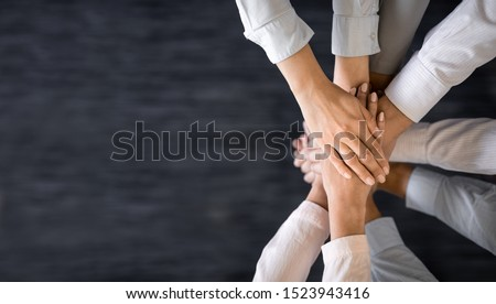 Close up top view of young business people putting their hands together. Stack of hands. Unity and teamwork concept. #1523943416