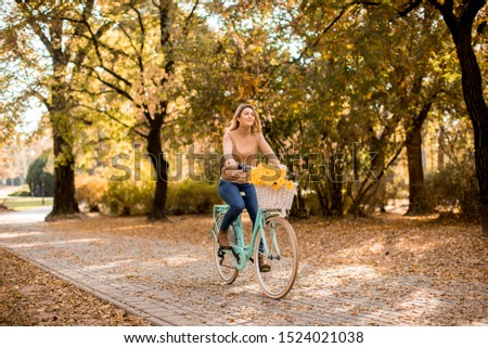 Attractive young woman riding bicycle in golden autumn park #1524021038
