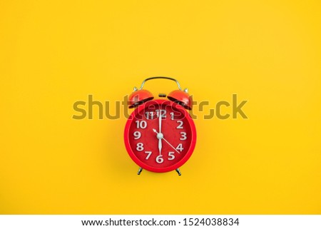Red alarm clock on yellow background. #1524038834