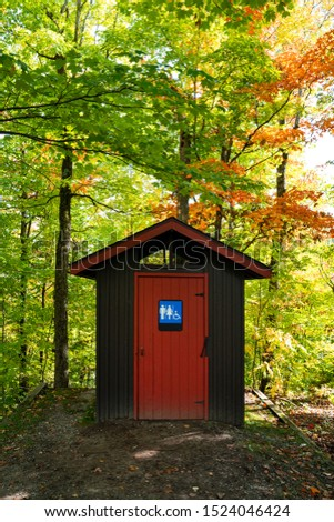 Gorgeous red and brown public toilet in the middle of the woods, Gatineau Park ,Quebec, Canada.
