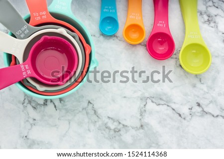 Set of measuring cups and measuring spoons use in cooking and baking lay on marble tabletop in flat lay design #1524114368