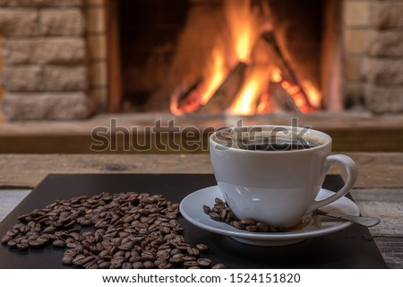 Cozy scene before fireplace with a cup of coffee, coffee beans, in country house, winter vacation and christmas concept.