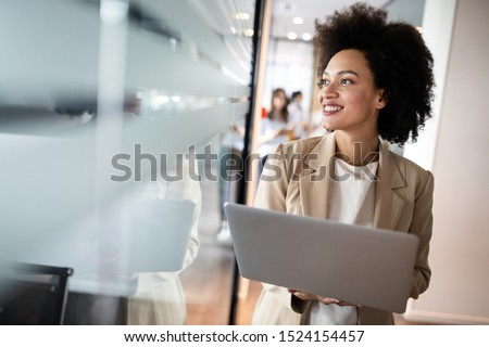 Portrait of an attractive young african businesswoman smiling while standing by windows in office #1524154457