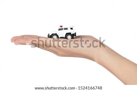 Hand holding Police Car Toys isolated on a white background.