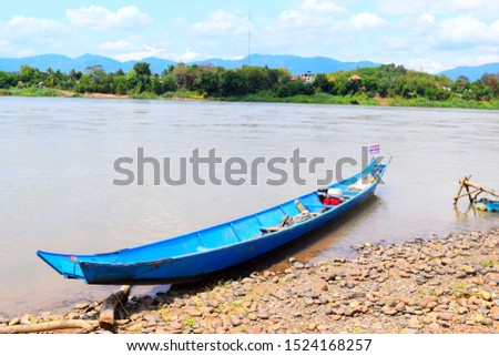 this pic show the local wooden boats mooring at beach port in riverside with mountain background, take photo frome Mekong river Thailand