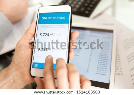 Hands of businessperson holding smartphone while scrolling through online banking account by workplace #1524183500