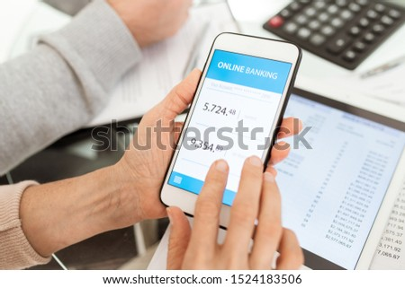 Hands of mature female holding smartphone with online account on its touchscreen over workplace #1524183506