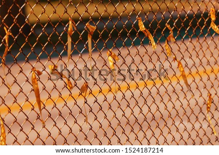 a rusty section of a rusty chain link fence with ribbons on it #1524187214