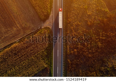 Truck on the road in sunset, top view of single transportation vehicle with trailer from drone pov #1524189419