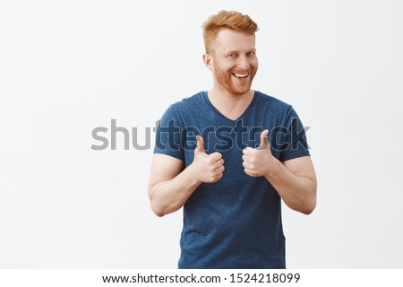 Nice job man, like it. Pleased good-looking happy male friend with ginger hair and brislte, showing thumbs up and smiling broadly, giving positive feedback, sharing his positive opinion over grey wall #1524218099