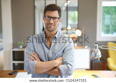 Cheerful man with eyeglasses standing in office #1524247331