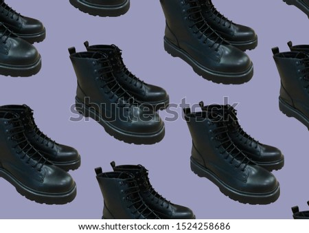 Black shiny polished black leather Marten boots shoes isolated on purple background. Fashionable punk historic British made leather boots. Banner concept. Copy space. Pattern