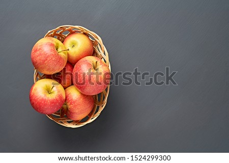 Lot of red fresh whole ripe apples full of vitamins lies in wooden wicker basket and old dark scratched concrete table on kitchen. Harvest or diet concept. Space for text. Top view #1524299300