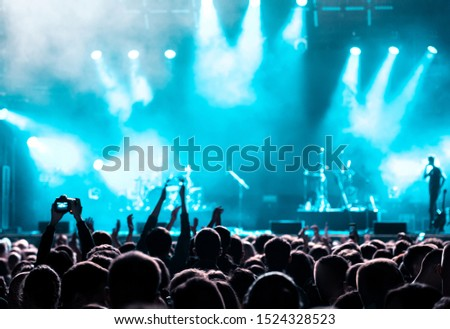 Rear view of audience crowd people fans raising hands shooting enjoying live music festival concert event concept rock band silhouettes performance sing on night club outdoor stage in spotlight light Royalty-Free Stock Photo #1524328523