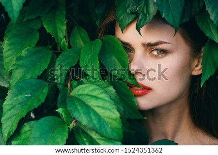 green leaves of bushes bright makeup red lips eye shadow eyelids close-up cropped view                                #1524351362