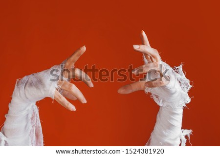 Halloween, costume image. The mummy's hand in bandages making gestures. The hand of the risen dead reaches up from the bottom, a bright orange background