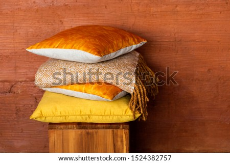 Stock of colorful pillows on wood chair against textured terracotta wall. Pile of soft yellow and orange cushions and blanket on stool near wall with space for text. Modern and cozy home concept. #1524382757