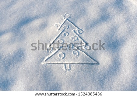 Christmas tree drawn on snow. Drawing on snow surface. Winter time, winter greetings. Fir tree with Christmas balls drawn on white snow. Christmas tree drawn on the snow. New Year's Eve. Copy space. #1524385436
